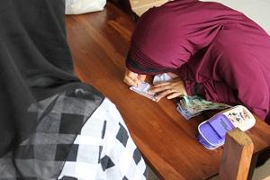 Panitia dari santi ibu-ibu yang membantu pasar murah, mencatat setiap nama yang datang di kertas kupon