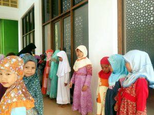 Santri puteri kelas TK/ PAUD yang sedang menghafal hadits sambil berdiri.